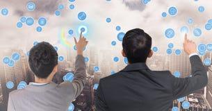 Unternehmensleiter, die Technologieikonen gegen Stadtbild berühren Lizenzfreies Stockbild