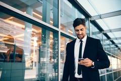 Unternehmensleiter mit Handy am Flughafen stockfotos