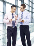 Unternehmensleute, die Geschäft am Flughafen besprechen Lizenzfreies Stockbild