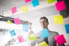 Unternehmensplanung mit Aufklebernotiz auf Glasmann zeigte auf Aufkleber im Büro Stockfotografie
