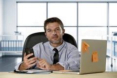Unternehmensporträt des glücklichen erfolgreichen Geschäftsmannes im Hemd und der Bindung, die am Computertisch mit Handy lächeln lizenzfreie stockfotografie