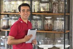 Unternehmer überprüfen Vorrat auf Kaffee in einem Glasregal unter Verwendung des Tablet-Computers, der Geschäftsmann, der Lagerun stockbilder
