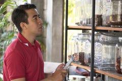 Unternehmer überprüfen Vorrat auf Kaffee in einem Glasregal unter Verwendung des Tabletten-PC, der Geschäftsmann, der Lagerung üb lizenzfreie stockbilder
