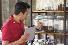 Unternehmer überprüfen Vorrat auf Kaffee in einem Glasregal unter Verwendung des Tabletten-PC, der Geschäftsmann, der Lagerung üb lizenzfreie stockfotografie