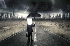 Unternehmer, der auf Straße mit Gewitter steht Stockfotografie