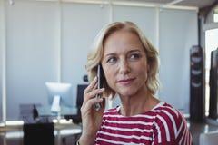 Unternehmer, der bei der Unterhaltung am Handy weg schaut Stockbilder