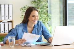 Unternehmer, der Dokumente online vergleichend arbeitet stockfotografie