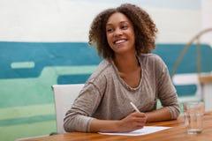 Unternehmer, der an einem Bürotisch lächelt Stockfotografie