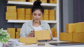 Unternehmer der jungen Frau, der Paketkästen in ihrem eigenen Jobkaufenden on-line-Geschäft überprüft stock footage