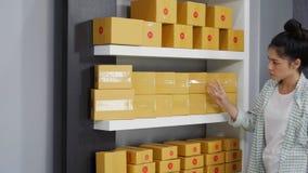 Unternehmer der jungen Frau, der Paketkästen in ihrem eigenen Jobkaufenden on-line-Geschäft zählt stock video footage