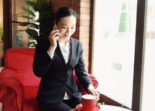 Unternehmer, der mit einem Telefon und einem Laptop in einer Kaffeestube arbeitet Lizenzfreie Stockfotografie
