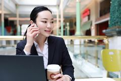 Unternehmer, der mit einem Telefon und einem Laptop in einer Kaffeestube arbeitet Lizenzfreies Stockfoto