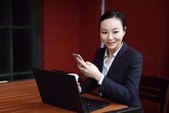 Unternehmer, der mit einem Telefon und einem Laptop in einer Kaffeestube arbeitet Lizenzfreie Stockfotos