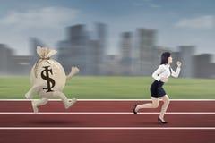 Unternehmer, der von einer Tasche des Dollars entgeht Lizenzfreie Stockfotos