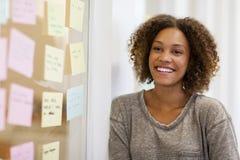 Unternehmer, der vor ihren Aufgabenkarten lächelt Stockfotos