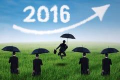 Unternehmer mit Regenschirm und Nr. 2016 am Feld Lizenzfreie Stockbilder