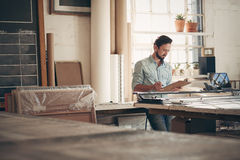 Unternehmer in seiner Werkstatt Zahlen auf einem Klemmbrett überprüfend stockfotos