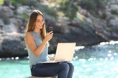 Unternehmerfrau, die mit einem Telefon und einem Laptop arbeitet Lizenzfreie Stockfotografie