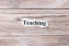 Unterricht des Wortes auf Papier Konzept Wörter des Unterrichtens auf einem hölzernen Hintergrund Lizenzfreie Stockfotografie
