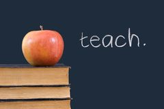 Unterrichten Sie geschrieben auf Tafel mit Apfel und Büchern Stockbilder