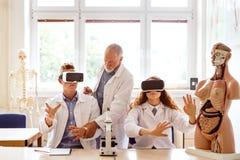 Unterrichtende Biologie des älteren Lehrers zu den hohen Schülern in der Arbeit lizenzfreie stockfotos