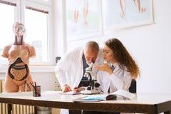 Unterrichtende Biologie des älteren Lehrers zum Studenten im Labor lizenzfreies stockbild