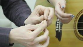 Unterrichtende Frau des Mannes, zum der Gitarre zu spielen stock footage