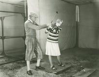 Unterrichtende Frau des Trainers, zum des Golfs zu spielen Lizenzfreie Stockfotografie