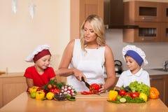 Unterrichtende Kinder der jungen Mutter, wie man Salat zubereitet stockfotografie