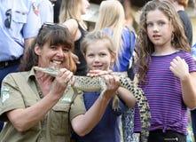Unterrichtende Kinder des australischen Frauen-Wildhüters der wild lebenden Tiere über gebürtige Krokodile an der lokalen Messe Lizenzfreie Stockfotos