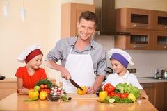 Unterrichtende Kinder des jungen Vaters, wie man Salat zubereitet Stockfotografie
