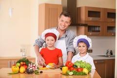 Unterrichtende Kinder des jungen Vaters, wie man Salat zubereitet Lizenzfreies Stockfoto