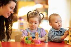 Unterrichtende Kinder des Lehrers spielen Spielzeug im Klassenzimmer Kindergartenvorschulekonzept lizenzfreie stockfotografie