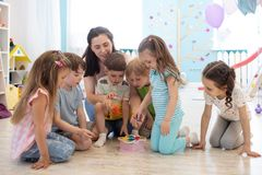 Unterrichtende Kinder des weiblichen Lehrers spielen Spielzeug im Klassenzimmer Kindergartenvorschulkonzept stockbild