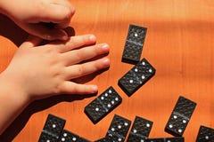Unterrichtende Kinder, zum des Dominospiels auf einem hölzernen Hintergrund zu spielen lizenzfreie stockfotos