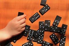 Unterrichtende Kinder, zum des Dominospiels auf einem hölzernen Hintergrund zu spielen lizenzfreie stockbilder