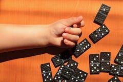 Unterrichtende Kinder, zum des Dominospiels auf einem hölzernen Hintergrund zu spielen lizenzfreies stockfoto