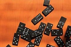 Unterrichtende Kinder, zum des Dominospiels auf einem hölzernen Hintergrund zu spielen stockfotografie