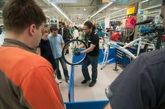 Unterrichtende Leute des Mechanikers, wie das Rad hergestellt ist Stockfoto