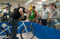 Unterrichtende Leute des Mechanikers, wie man die Bremsen auf einem Fahrrad justiert Stockfotos