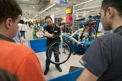 Unterrichtende Leute des Mechanikers, wie man die Bremsen auf einem Fahrrad justiert Lizenzfreies Stockfoto
