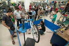 Unterrichtende Leute des Mechanikers, wie man ein Fahrrad repariert Lizenzfreies Stockbild