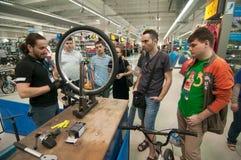 Unterrichtende Leute des Mechanikers, wie man ein Fahrradrad auf einem ausrichtenden Stand ausrichtet Stockfoto