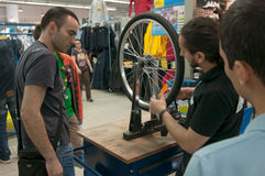 Unterrichtende Leute des Mechanikers, wie man ein Fahrradrad auf einem ausrichtenden Stand ausrichtet Lizenzfreies Stockfoto