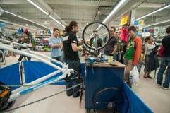 Unterrichtende Leute des Mechanikers, wie man ein Fahrradrad auf einem ausrichtenden Stand ausrichtet Stockbild