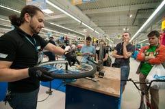 Unterrichtende Leute des Mechanikers, wie man ein Fahrradrad ohne einen ausrichtenden Stand ausrichtet Lizenzfreie Stockfotos