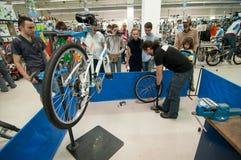 Unterrichtende Leute des Mechanikers, wie man einen Reifen aufbläst Stockfoto
