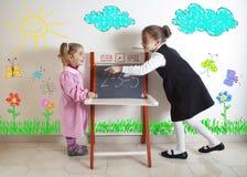 Unterrichtende Mathematik des kleinen Mädchens zu einem jüngeren Kind stockfotografie