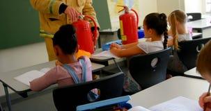 Unterrichtende Schulkinder des m?nnlichen kaukasischen Feuerwehrmanns ?ber Brandschutz im Klassenzimmer 4k stock video footage