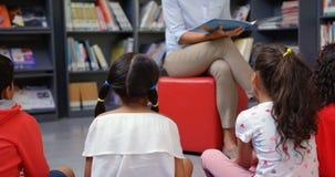 Unterrichtende Schulkinder des weiblichen Lehrers in der Schulbibliothek 4k stock video
